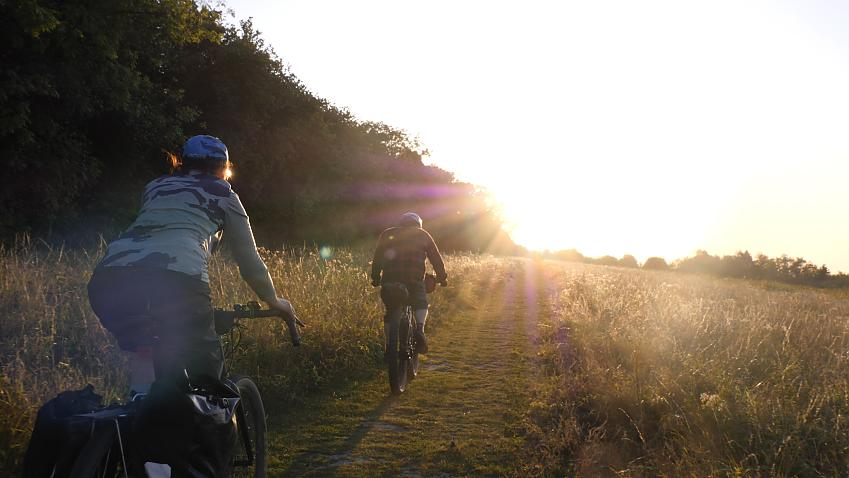 Two cyclists heading west into the sunset