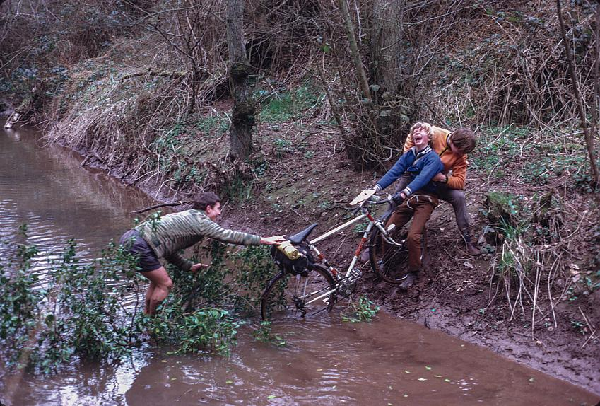 A cyclist is helped pulling their bike out of a river