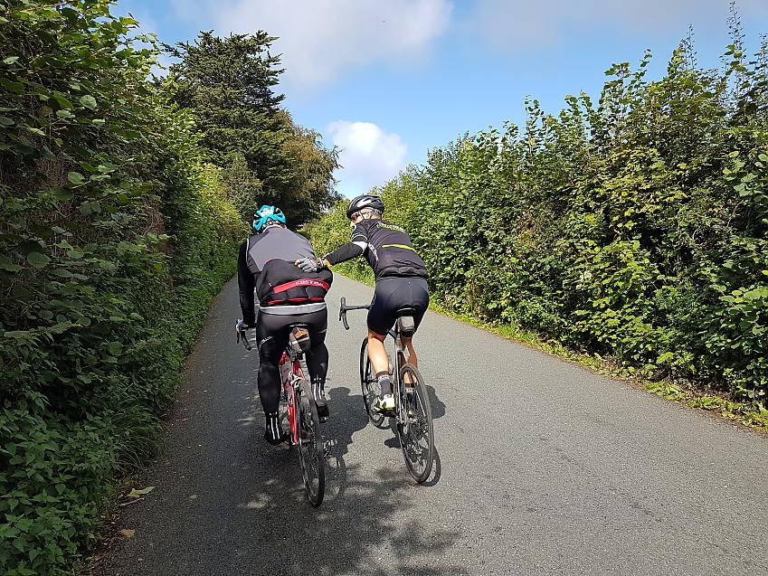 Cyclist getting a helping hand up the hill