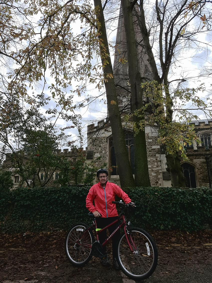 A middle-aged woman in red cycling kit stands by the roadside with a church tower in the background