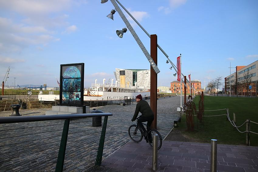 A man on a bicycle rides into a dockland area with a large ship visible in the background