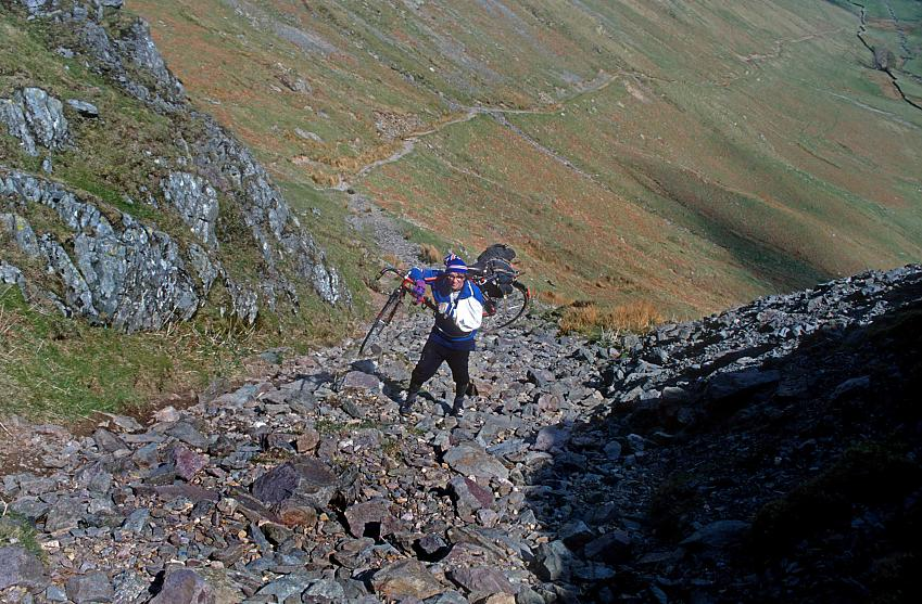 A cyclist with a broken arm carries his bike up a stoney track
