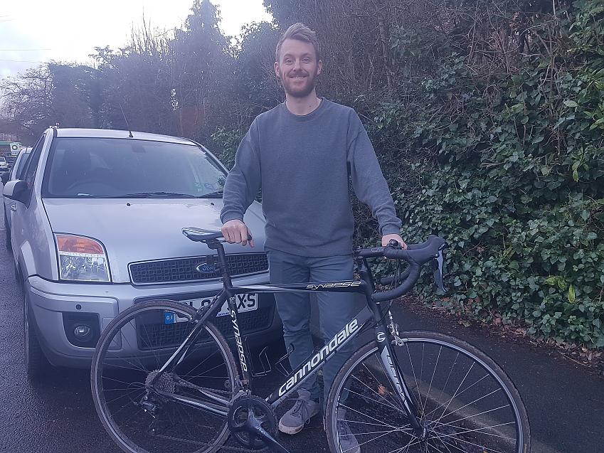 A man stands with his bike in front of a car