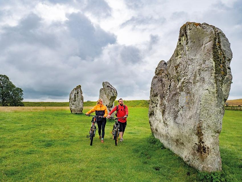 A woman and a man walk through a field dotted with stone monuments towering above them. They are both wheeling bicycles.
