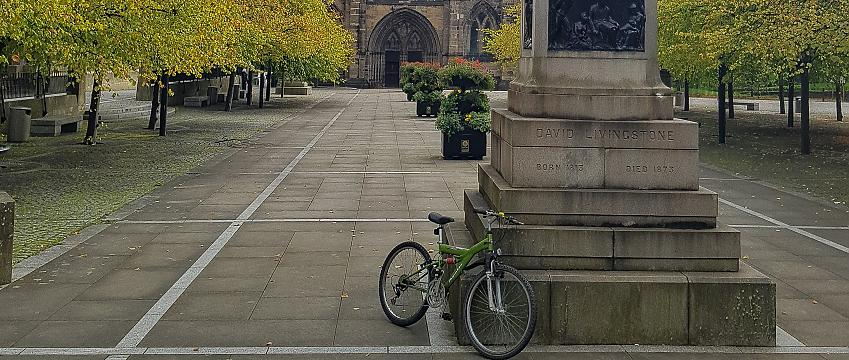 bike sitting against the base of a monument in a city centre