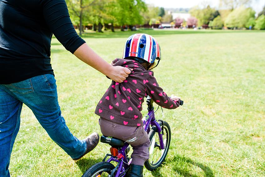 Lightly holding the back of a child's jumper can help them to learn to cycle