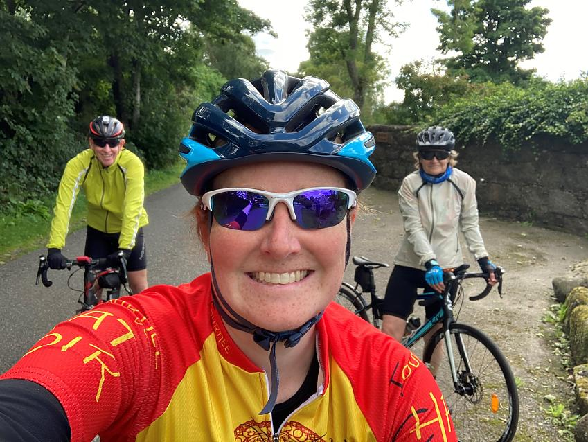 Woman with parents all on road bikes in rural setting