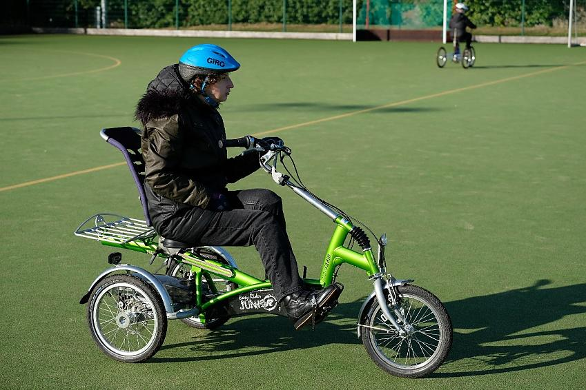 Woman riding trike on playing field