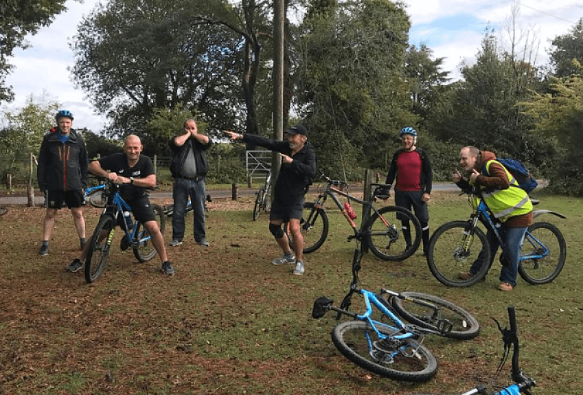 A group of cyclists striking poses for the camera as they have their photograph taken in the part