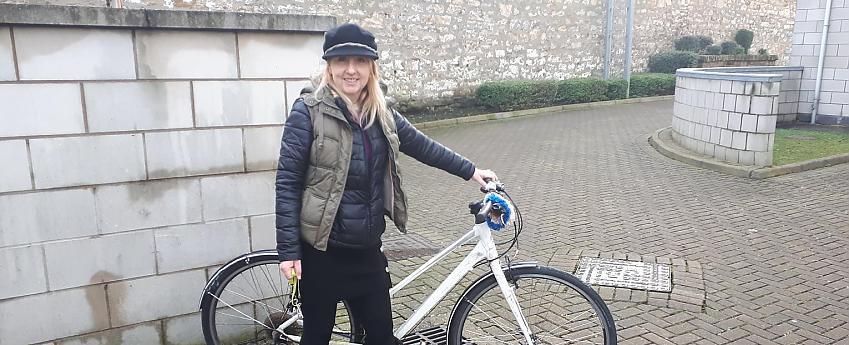 women standing with bike in urban setting