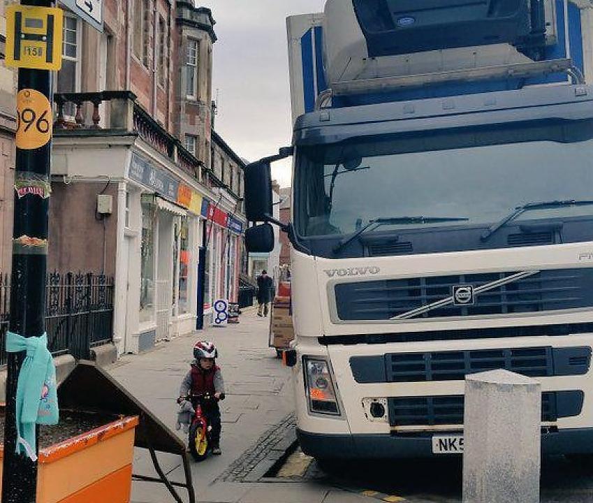 A small child on a balance bike beside a huge lorry
