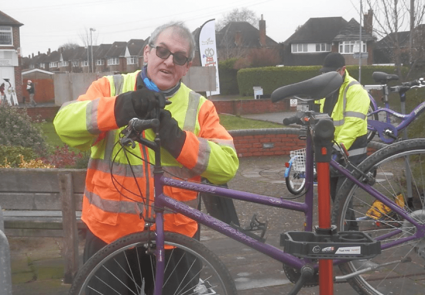 An older man in an orange and yellow jacket carries out repairs on a bicycle. Another person is stood behind him but not facing the camera