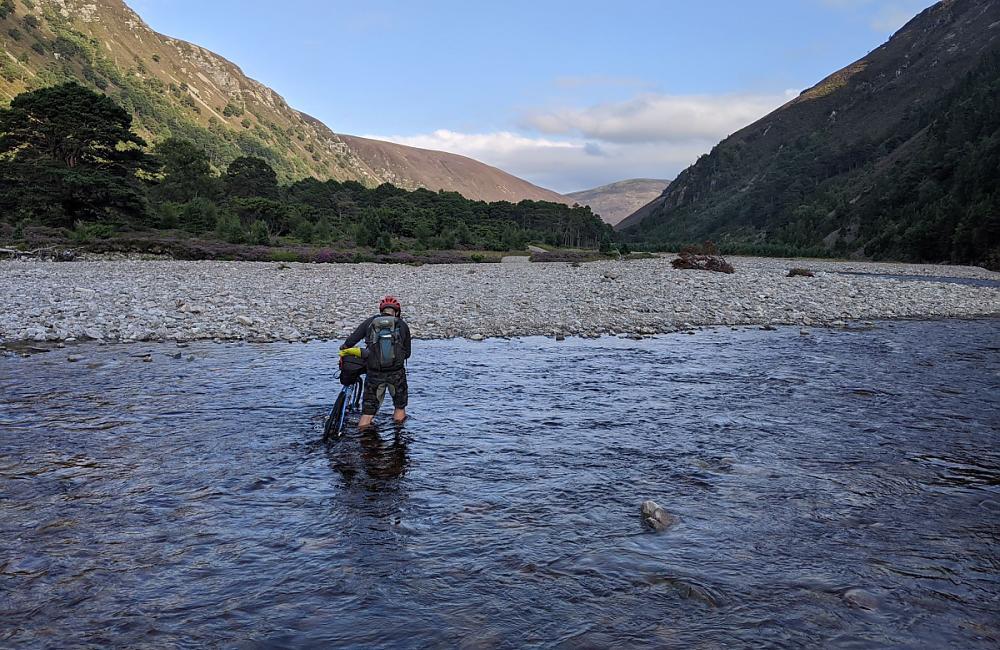 A cyclist wades across a river