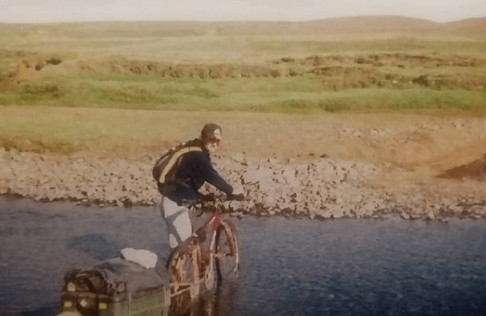 A cyclist crosses an Icelandic river with a cycle trailer
