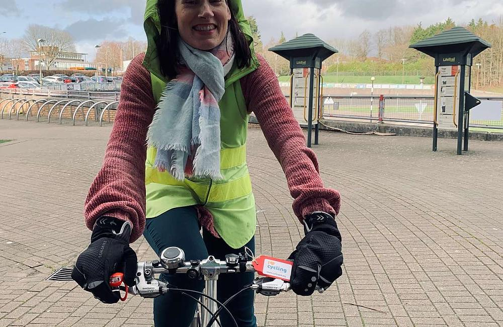 A woman facing head on to the camera standing with one foot on the floor and another on the pedal of her bicycle