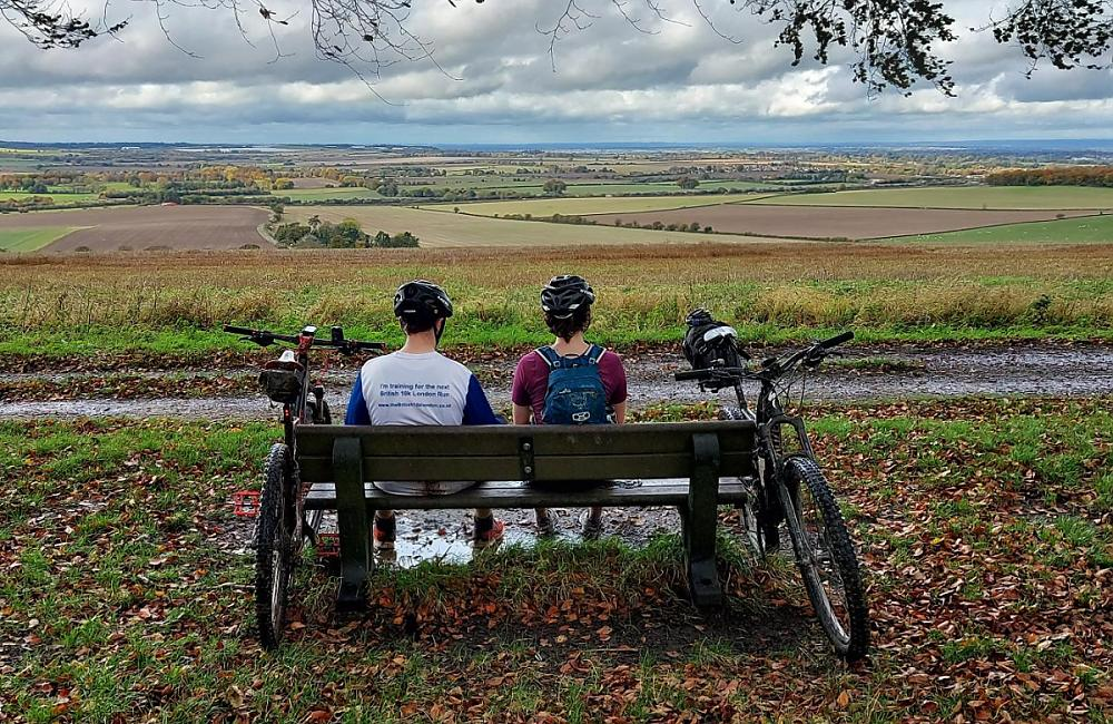 Two cyclist look out from King Alfreds Way sat on a bench