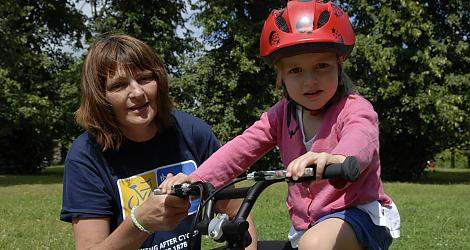 Julie teaches a four year old girl to learn to ride a bike