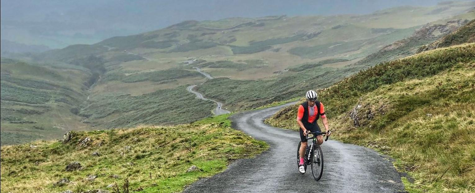 A person is cycling up a hill in an undulating landscape