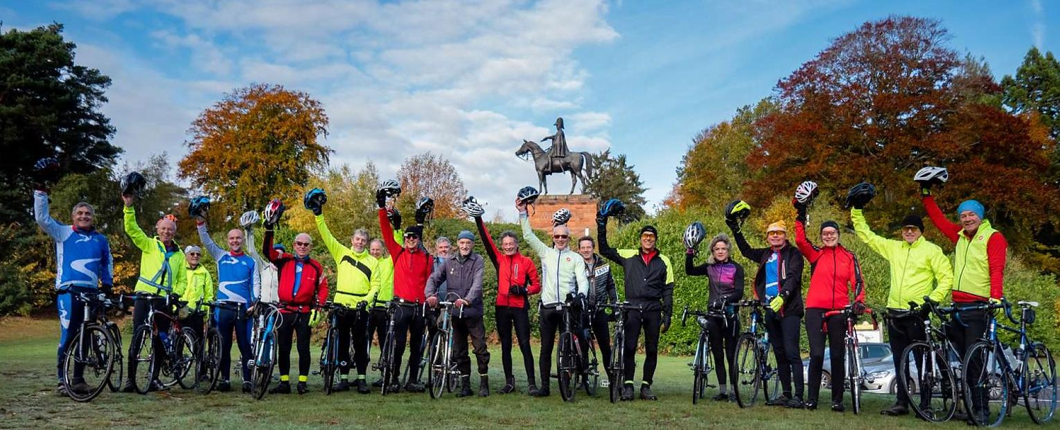 A group of cyclists standing in a line in front of a statue